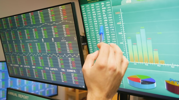 Close up of stock market trader hand on monitors with financial graphs. economy crash.
