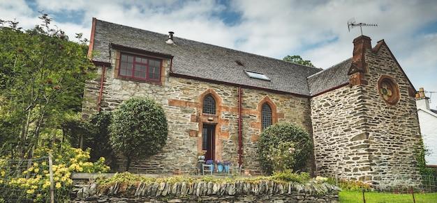근접 돌 고 대 집입니다. 북아일랜드. 빈티지 스타일의 지역 건축입니다. 정원으로 둘러싸인 멋진 건물 입구. 아늑한 안뜰. 전통적인 아일랜드 스타일.