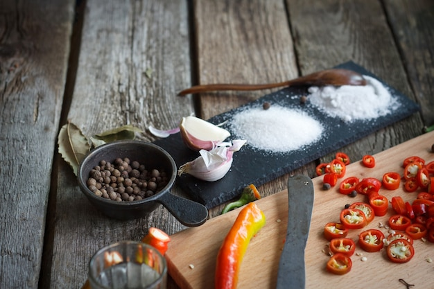 Close-up of stone stand with heaps of salt, sugar, garlic, allspice, bay leaf next to a board with chopped chili peppers on an old wooden surface