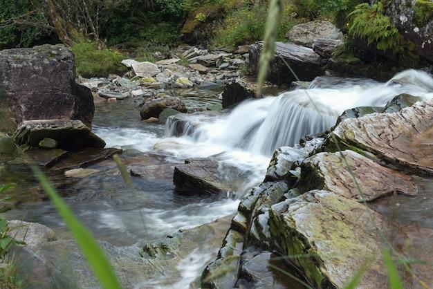 長時間露光の凍った水の流れと山川の石を閉じる