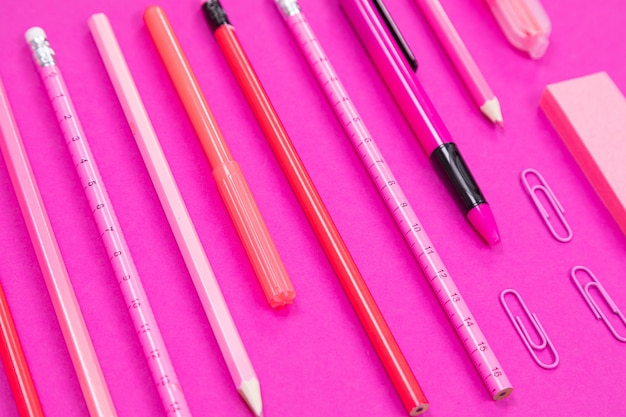Close up of straightly arranged group of pink color writing equipment on pink surface isolated