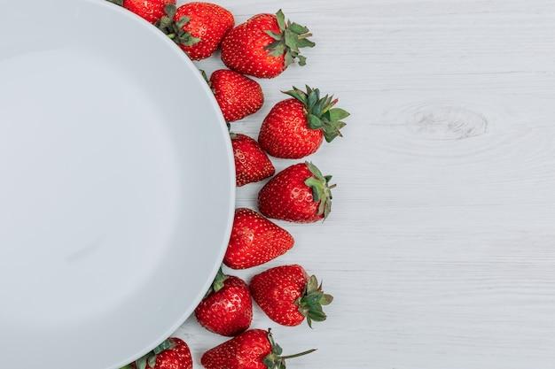흰색 나무 배경에 빈 접시와 근접 딸기. 텍스트의 가로 복사 공간