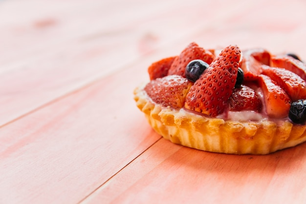 Close-up of strawberry tart on wooden background