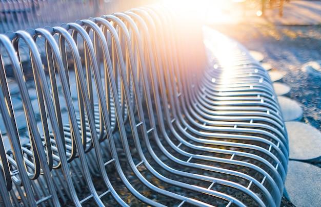 Металлические трубы уличные скамейки крупным планом, расположенные параллельно друг другу на уличной конструкции. концепция атмосферостойких материалов и современного промышленного дизайна. место для рекламы
