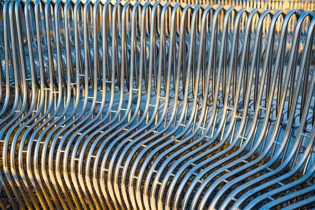 通りの構造物に互いに平行に配置されたクローズアップのストリートベンチの金属パイプ。耐候性素材とモダンな工業デザインのコンセプト。