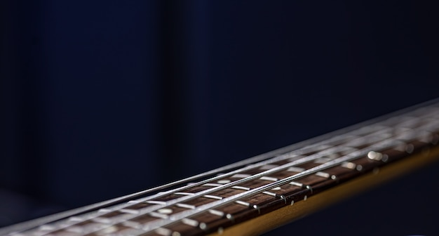 Close up of strings on bass guitar on blurred black background copy space.