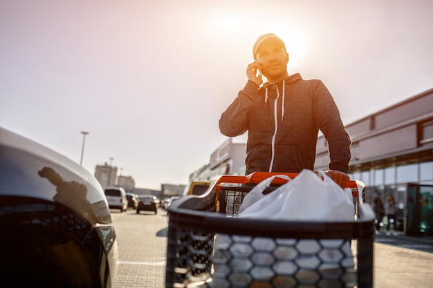 Close-up of a stroller with food near a large supermarket in a suburban shopping center. a man stands near a car in a parking lot after a successful shopping