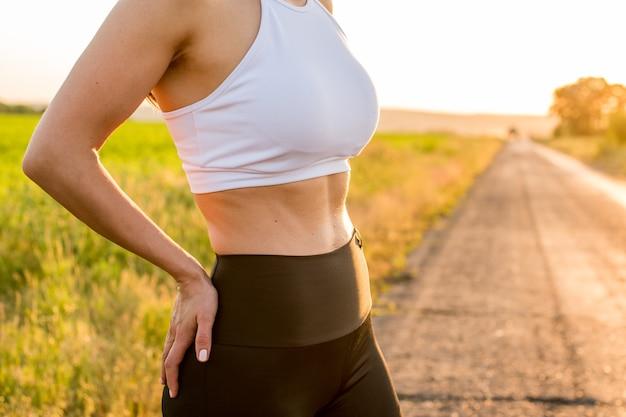 Крупным планом показывает сильный пресс. молодой фитнес спортивный женщина позирует в спортивной одежде и расслабляющий после тренировки.