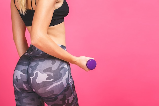Close-up of strong fit young woman with dumbbell isolated on a pink background
