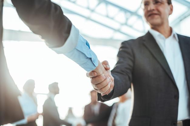 Закройте вверх. крепкое рукопожатие деловых людей на фоне офиса. концепция партнерства