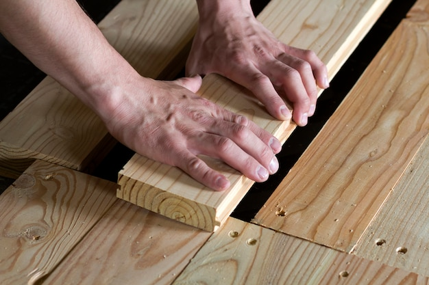 Close up of strong muscular hands of professional carpenter installing natural wooden new planks on wooden frame floor reconstruction, improvement, renovation and carpentry concept.