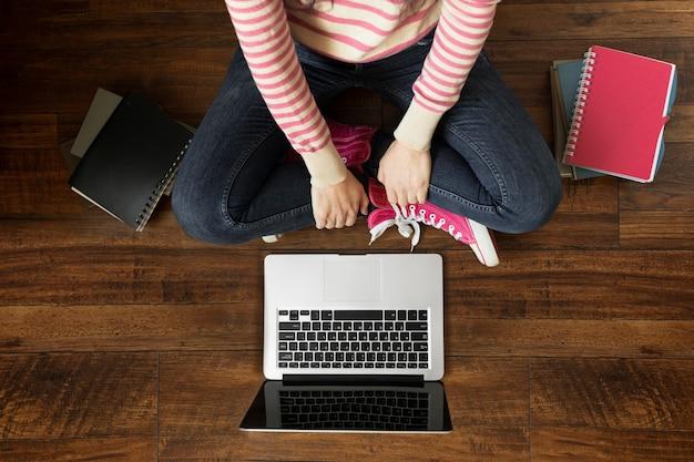 Primo piano studente sul pavimento con il computer portatile