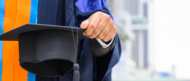 Close up of student holding mortarboard on graduation day