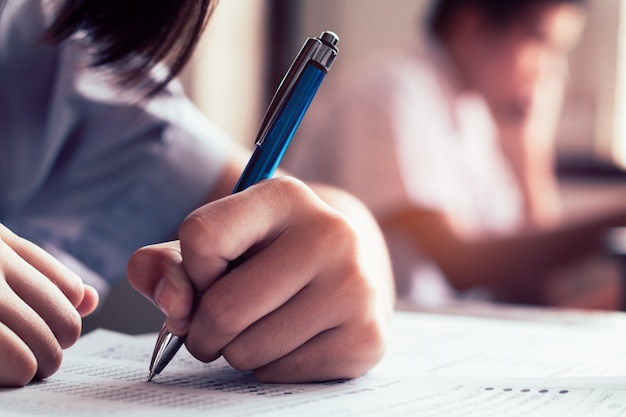 Close-up to student holding pen and writing final exam