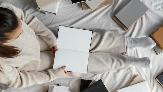 Студент в постели с плоской кладкой книг крупным планом