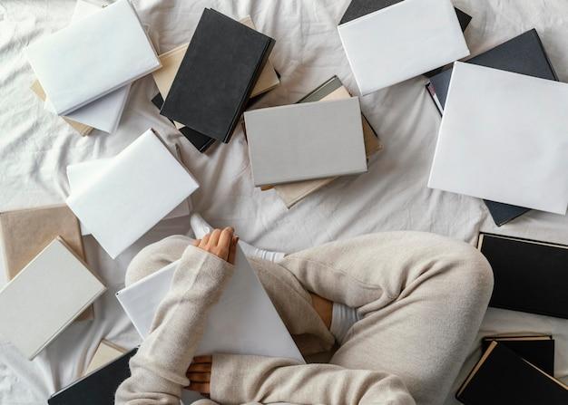 Студент в постели с книгами крупным планом