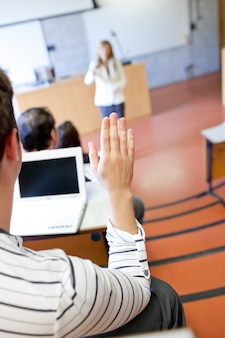 Close up of a student raising his hand during a lesson
