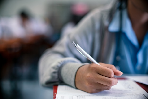 Close up students writing for exam