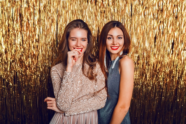 Close up studio image of two amazing sexy celebrating girls  with red lips, surprise face,