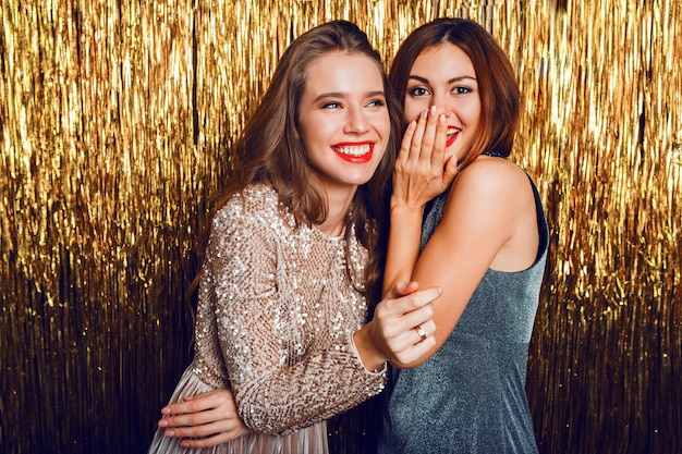 Close up studio image of two amazing sexy celebrating girls  with red lips,