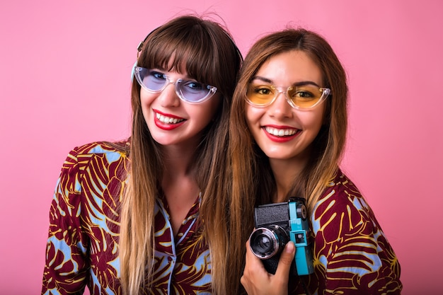 Close up studio lifestyle portrait of pretty two friends wearing printed matching outfits and sunglasses, holding vintage camera