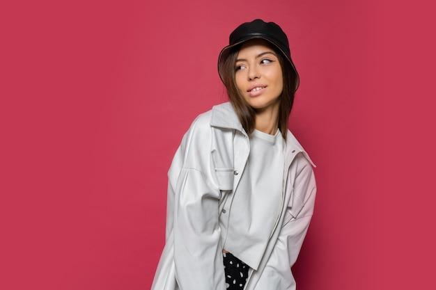 ピンクの背景にポーズをとってスタイリッシュなキャップと白いジャケットに身を包んだ完璧な笑顔で美しい女性のスタジオポートレートを閉じます。分離します。