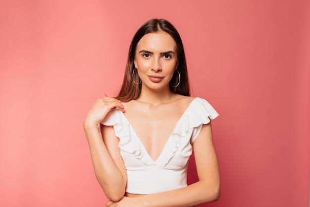 孤立したピンクの壁にポーズをとってスタイリッシュな美しい女性のスタジオポートレートを閉じる