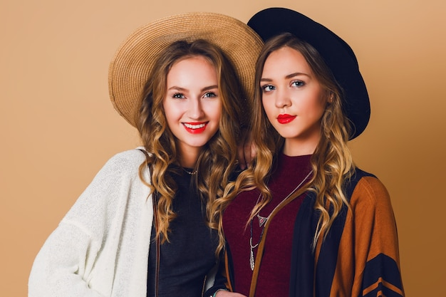 Close up studio portrait of two  sisters with blond wavy hairstyle in wool and straw hat wearing striped poncho