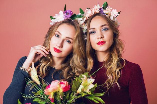 Chiuda sul ritratto dello studio di due giovani donne bionde graziose nell'ira dei fiori di primavera, l'acconciatura lunga ondulata stupefacente, il trucco luminoso, esaminando la macchina fotografica.