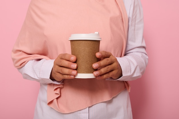 Close-up studio shot of female hands holding a craft takeaway cardboard cup with hot drink. cropped view of muslim woman in hijab with disposable paper mug, isolated on pink background with copy space