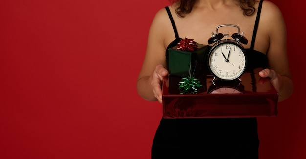 복사 공간이 있는 빨간색 배경에 격리된 이브닝 블랙 벨벳 드레스를 입은 자른 여성의 손에 반짝이는 선물 포장지에 있는 알람 시계의 클로즈업 스튜디오 샷