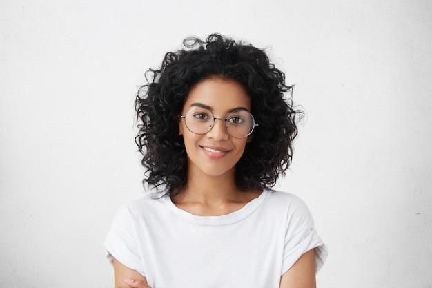 黒い巻き毛の美しい若い混血の女性モデルのスタジオ撮影を閉じる