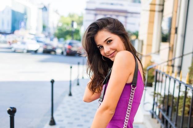 日当たりの良い通りを歩いて、日当たりの良い天気を楽しんで、買い物をして、週末に素晴らしい時間を過ごすために友達を待っている美しい女の子を閉じます。ウェーブのかかった髪型。紫色のベルベットのセクシーなドレス。ロマンチックな気分。