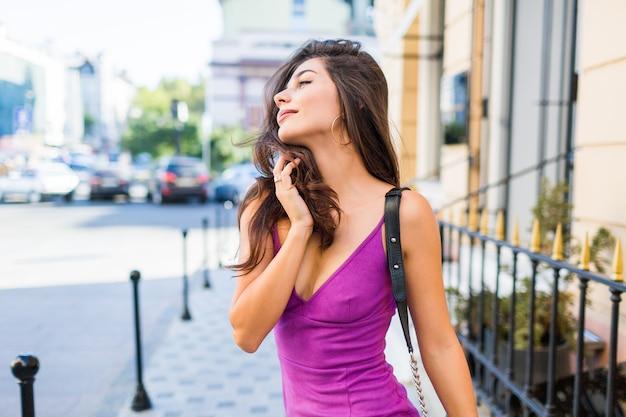 햇볕이 잘 드는 거리를 걷고, 햇볕이 잘 드는 날씨를 즐기고, 쇼핑을하고, 주말에 좋은 시간을 보내도록 친구를 기다리는 멋진 소녀를 닫습니다. 물결 모양의 헤어 스타일. 퍼플 벨벳 섹시 드레스. 낭만적 인 분위기.