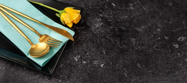 Close up of stylish black square plate and gold cutlery on black background