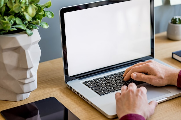 Close up of stylish composition with businessman mock up laptop screen and office supply template