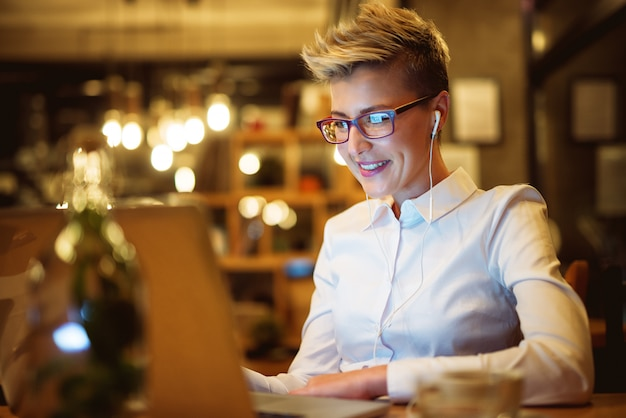 Close up of stylish confident short hair entrepreneur with eyeglasses and earphones relaxing with music while sitting in a cafe and working on a laptop