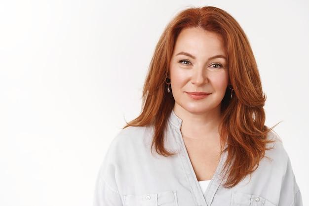 クローズアップスタイリッシュな自信を持って成功した見栄えの良い中年の赤毛の妻は、うれしそうに満足した表情のカメラのような誠実な信頼できる視線立っている白い壁の派手なブラウスを笑っています