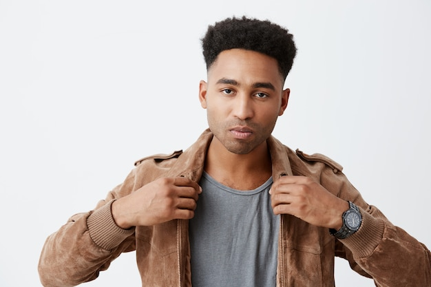 Close up of stylish dark-skinned male with afro hairstyle in gray t-shirt under fashionable brown jacket looking in camera with derious face expression, modeing for clothes brand photoshoot.