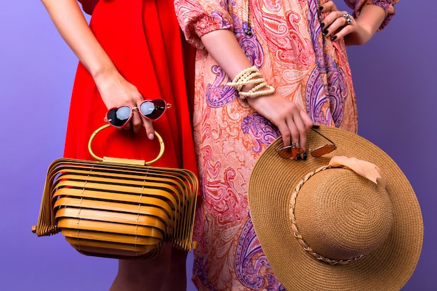 Close up stylish fashion details, two woman with bright dresses posing at purple background, holding sunglasses straw hat and super trendy modern wooden handbag.