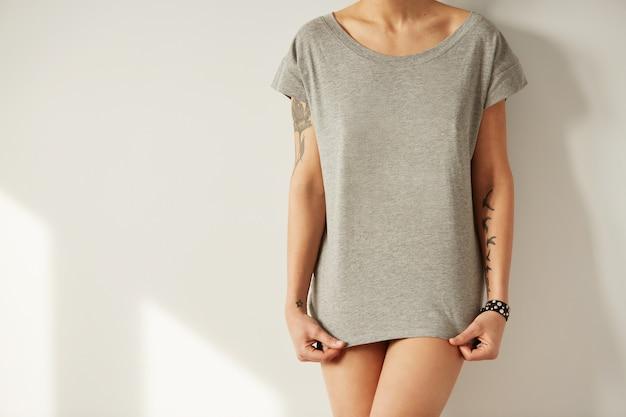 Chiuda sulla ragazza alla moda che indossa la maglietta in bianco e che osserva giù
