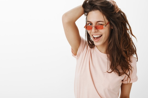 Close-up of stylish girl with sunglasses posing against the white wall