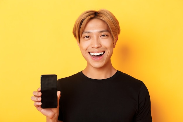 Close-up of stylish handsome korean guy showing smartphone screen and smiling pleased, recommend mobile app, standing over yellow wall