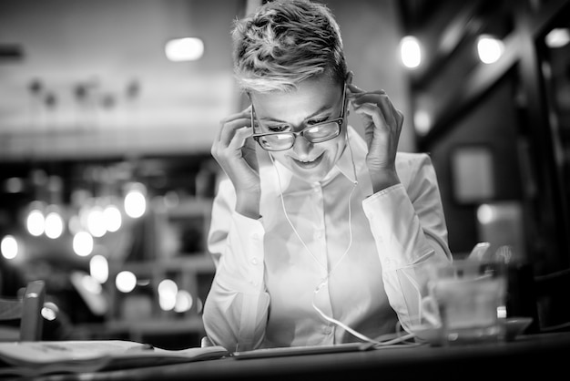 Close up of stylish happy entrepreneur with eyeglasses and earphones relaxing with music while sitting in a cafe in the night