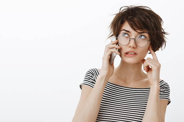 Close-up of stylish hipster woman talking on mobile phone in loud place, shut one ear to hear better
