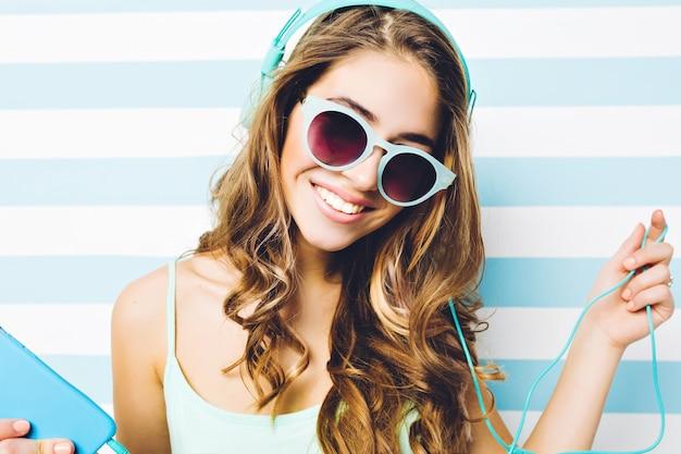 Закройте стильный летний портрет молодой привлекательной женщины с длинными вьющимися волосами в синих солнцезащитных очках, слушая музыку через наушники на полосатой бело-голубой стене. улыбка, счастье.