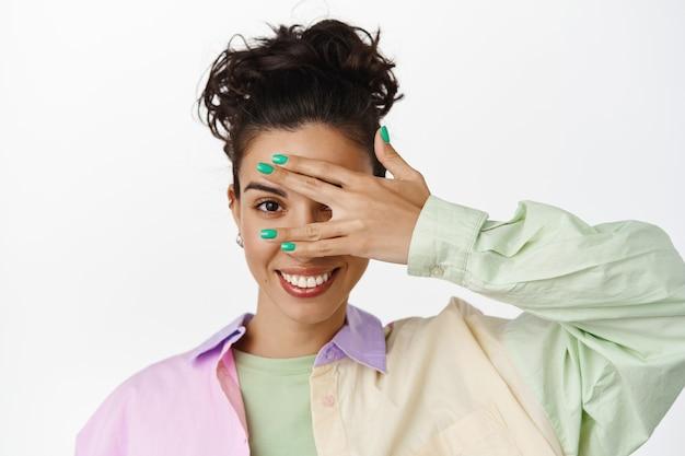 Primo piano di una giovane ragazza moderna ed elegante, con occhi, sbirciare attraverso le dita e denti bianchi sorridenti, in piedi con una camicia alla moda su bianco