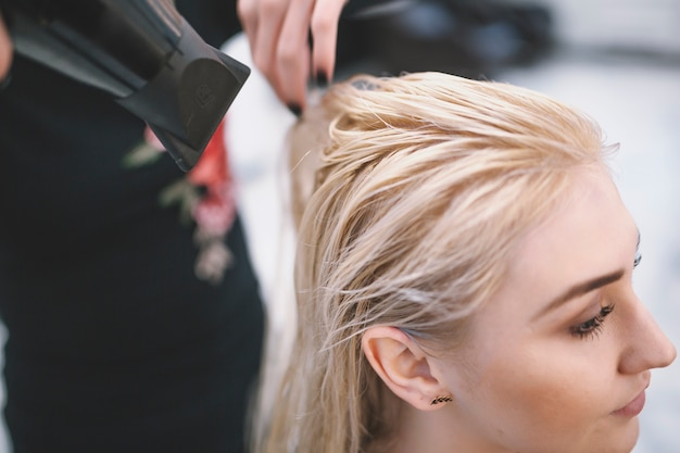 Close-up of stylist drying wet hair