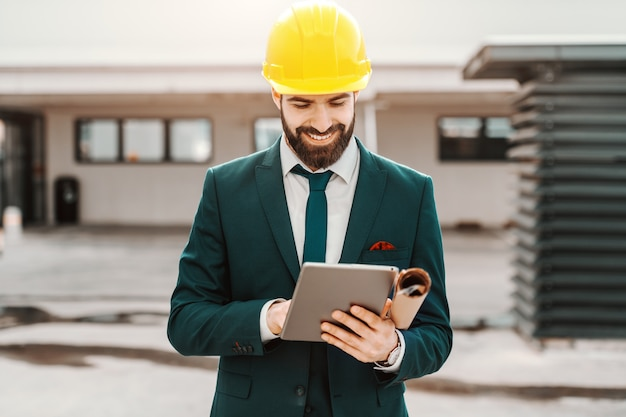 Close up of successful architect in formal wear and yellow helmet using tablet. under armpit plans.