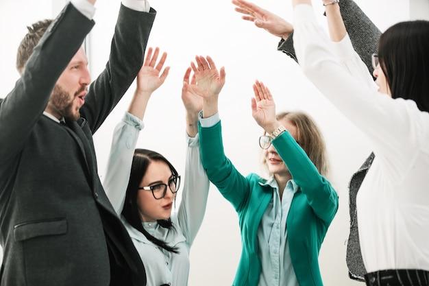 クローズアップ。成功したビジネスチームがオフィスに立ち、手を挙げます。チームワークの概念